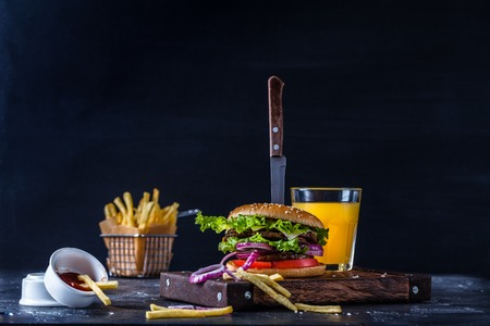 hamburger on a black background with French fries and orange juice, horizontally, wooden board, copyspace