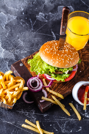 hamburger on a black background with French fries and orange juice, vertically, wooden board, copyspace