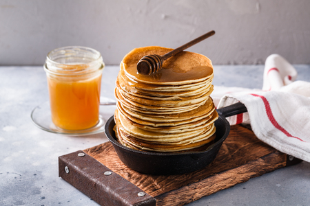 Pancakes with honey on a gray background, horizontally, copyspace