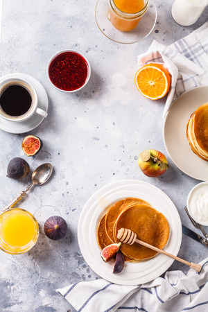 Pancakes with honey, fruit and coffee on a gray background, vertically, figs, alginate juice, raspberry jam, sour cream, flat lay, copyspace Stok Fotoğraf