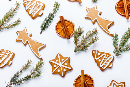 flat lay of Christmas cookies, dried orange and fir branches on a white background, square