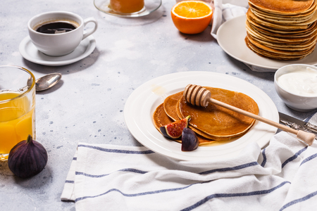 Pancakes with honey, fruit and coffee on a gray background, horizontally, figs, alginate juice, raspberry jam, sour cream, flat lay, copyspace