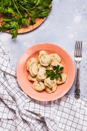 Boiled dumplings in a pink plate on a gray background, parsley, vertically, flat lay Stok Fotoğraf