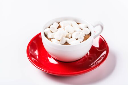 Hot chocolate and marshmelow in a white cup on a red plate on a knitted warm blanket. horizontal, Christmas