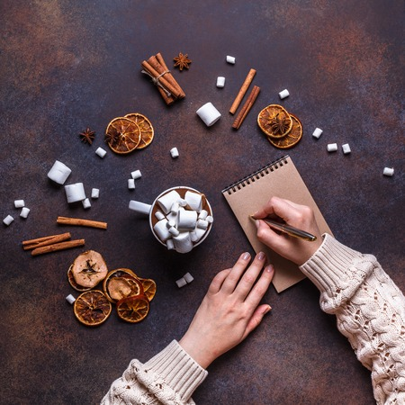 Christmas cookies in a white wooden box with hot chocolate and marshmelow, on a dark background, square, flat lay, hands, kraft paper, notebook