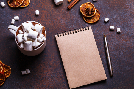Christmas cookies in a white wooden box with hot chocolate and marshmelow, on a dark background, square, flat lay, kraft paper, notebook