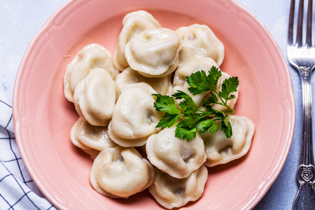 Boiled dumplings in a pink plate on a gray background, parsley, horizontal, flat lay Stok Fotoğraf