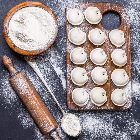 Raw dumplings on a black background, flour, rolling pin, spoon, square, flat lay
