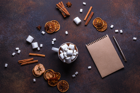 Christmas cookies in a white wooden box with hot chocolate and marshmelow, on a dark background, horizontal, flat lay, kraft paper, notebook