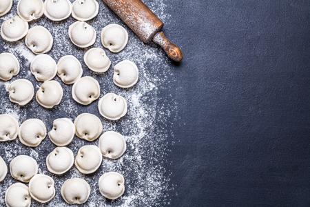 Raw dumplings on a black background, flour, rolling pin, spoon, flat lay, horizontally Stok Fotoğraf