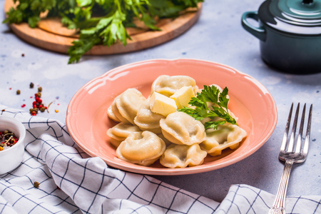 Boiled dumplings in a gray plate on a gray background, parsley, horizontal, flat lay, copyspace