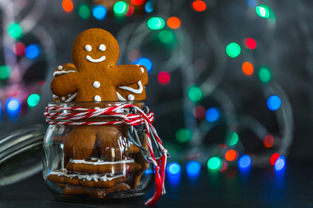 a christmas cookie a man in a glass jar, against a background of a colorful New Years garland, bokke, horizontally, copyspace