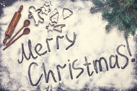 The text of a Merry Christmas from flour on a black background, horizontally, flat lay Stok Fotoğraf