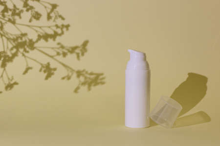 Beauty cosmetic cream, scincare, serum bottle on yellow background with dry flowers shadow. Blank label for branding mock up, front view