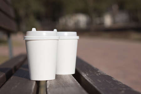 Two white take away cups of tea or coffee on a dark aged wooden surface with a copy space for your text, front view