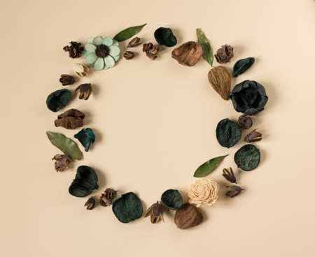A wreath with dry flowers and leaves on a beige background with a copy space for your text