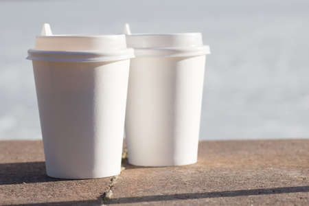 Two white take away cups of tea or coffee on a concrete surface with a copy space for your text, front view Foto de archivo