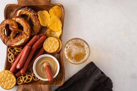 Snack to beer, Bavarian sausages, chips, brezels, crackers and mustard. Oktoberfest food, appetizing beer snacks set for big company.
