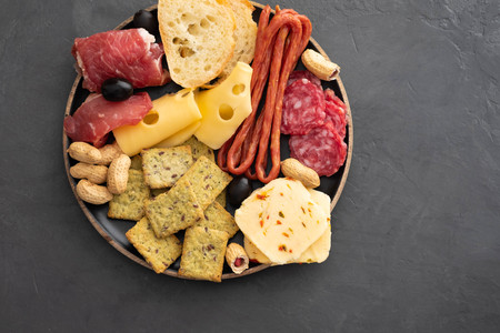 Meat and cheese plate.Traditional italian antipasto, cutting board with salami, cold smoked meat, prosciutto, ham, cheeses, olives, capers. Cheese and meat appetizer. Top view