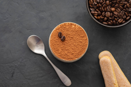 Delicious Italian dessert tiramisu, chocolate, cocoa and coffee beans on a black background. Top view with copy space. Stock Photo