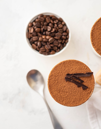 Tiramisu in a glass with coffee beans on white background. Copy space. Top view. Stock Photo