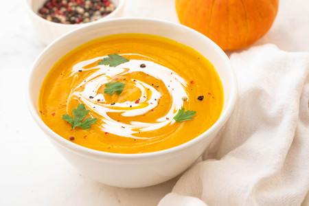 Pumpkin soup with cream and pumpkin seeds isolated on white background. Autumn concept. Stockfoto