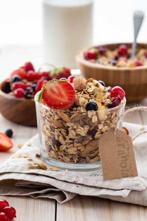 Homemade granola in open glass jar on rustic wooden background. Copy space.
