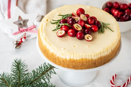 Cheescake with fresh cranberry and rosemary. Christmas cake with decoration on white background. Stock fotó
