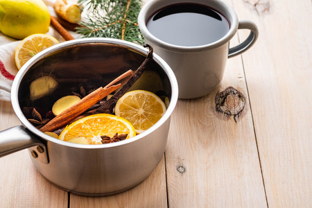 Mulled wine hot drink with citrus, apple and spices in aluminum casserole and Fir branch on background. 版權商用圖片