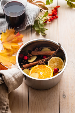 Mulled wine hot drink with citrus, apple and spices in aluminum casserole and Fir branch on background. Imagens