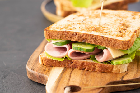Close-up photo of a club sandwich. Sandwich with meet, prosciutto, salami, salad, vegetables, lettuce on a fresh sliced bread on wooden background.