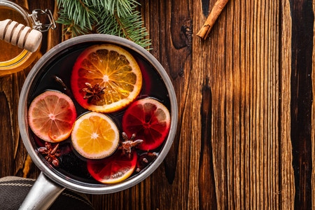 Mulled wine hot drink with citrus, apple and spices in aluminum casserole and Fir branch on background. Stok Fotoğraf