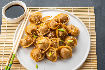Home made chinese and korean dumplings served on the traditional steamer and bamboo mat decorated with soy sauce, parsley, giner.