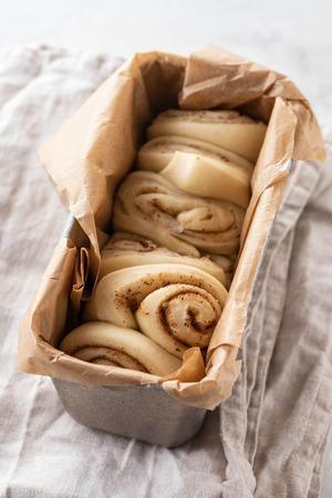 Raw cinnamon bread in a baking dish. Copy space.