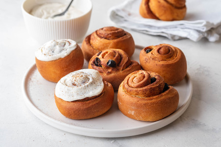 Delicious Cinnamon Rolls with cheese cream on a white plate. Copy space.