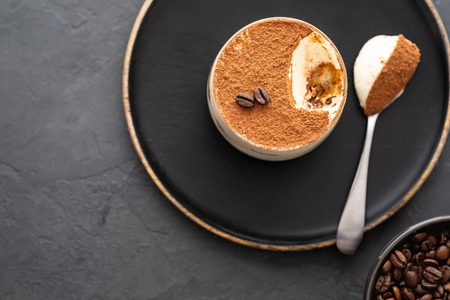 Delicious Italian dessert tiramisu, chocolate, cocoa and coffee beans on a black background. Top view with copy space. Banque d'images