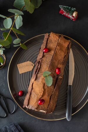 Traditional Christmas dessert, Christmas yule log cake with chocolate cream, cranberry and rosemary twigs. On stone gray background with Christmas tree branches, copy space top view Imagens