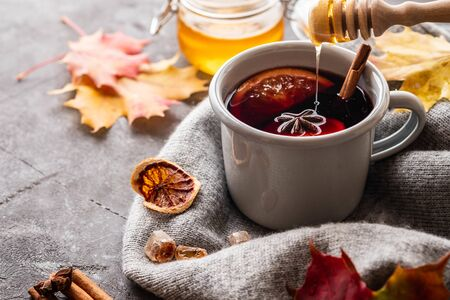 Mulled wine in grey rustic mugs with spices and citrus fruit.