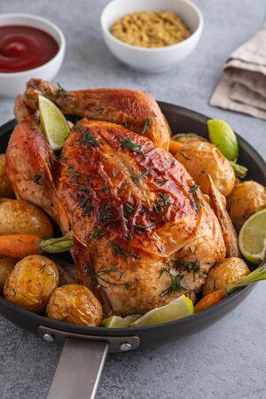 Pollo arrosto intero. Servito su un piatto con verdure e patate al forno. Vista frontale. Archivio Fotografico