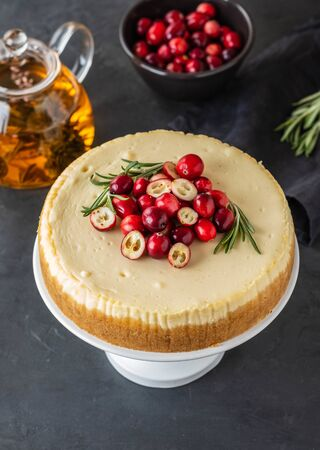 Classic cheesecake with cranberries and rosemary on a dark background. Winter version of cheesecake. Stok Fotoğraf