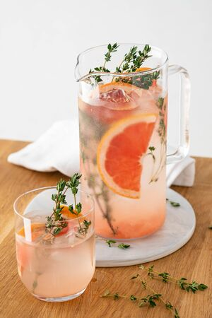 Lemonade with grapefruit and thyme in a glass jug on light background. Copy space. Banque d'images - 131812864