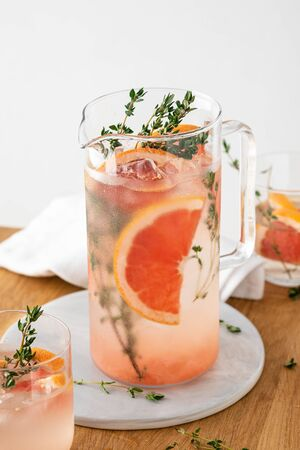 Lemonade with grapefruit and thyme in a glass jug on light background. Copy space. Banque d'images - 131812866