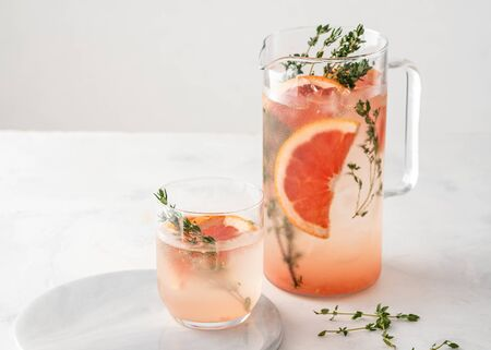 Lemonade with grapefruit and thyme in a glass jug on light background. Copy space. Banque d'images - 131812868