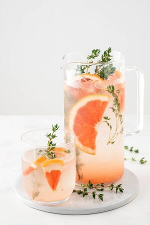 Lemonade with grapefruit and thyme in a glass jug on light background. Copy space. Banque d'images - 131812875
