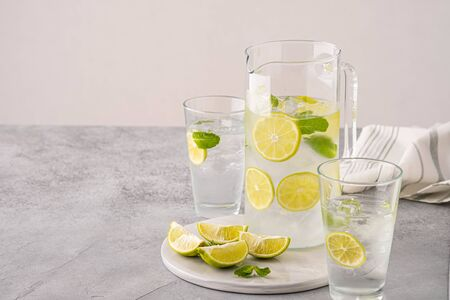 Fresh lemonade with lime and ice cubes in a sugar rimmed glass on wood with limes.