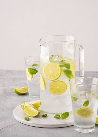 Fresh lemonade with lime and ice cubes in a sugar rimmed glass on wood with limes. Banque d'images - 131812912
