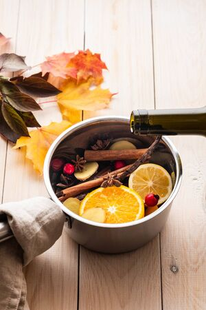 Mulled wine hot drink with citrus, apple and spices in aluminum casserole and Fir branch on concrete background.