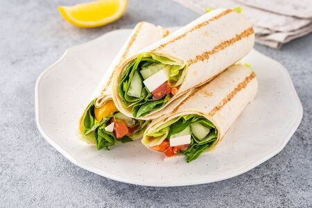 Wrap sandwich, roll with fish salmon and vegetables. Grey background. Close up.