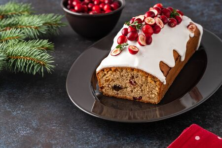 Christmas cake with cranberries and Christmas decorations on a dark background. Copy space.