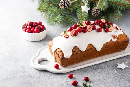 Christmas cake with cranberries and Christmas decorations on a gray background. Copy space. 免版税图像